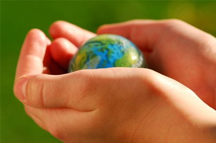 a pair of hands holding a miniature globe