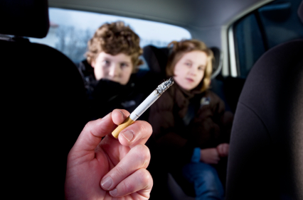 adult smoking with kids in the backseat of car