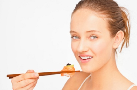 a young woman eating sushi