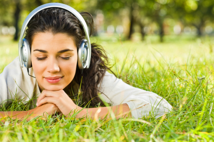 woman with headphones on in a field